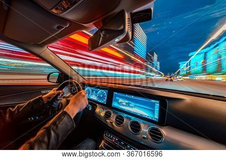 Movement Of The Car At Night At High Speed View From The Interior With Driver Hands On Wheel. Concep