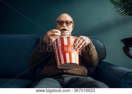 Elderly man with popcorn watching TV on couch