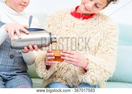 Health Conscious Teenager With Reusable Water Bottle Pouring Tea Into Reusable Cup. Young People And