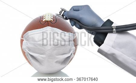 Covid-19 and Sports Concept. An American Football With Surgical Mask and a doctors hand holding a stethoscope to the ball to check its condition.