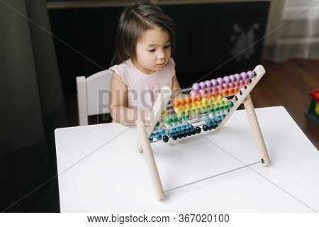 Cute Little Two-year-old Girl Wearing White Dress Is Playing With Multicolored Abacus. Child Is Acco
