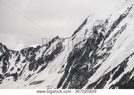Atmospheric Minimalist Alpine Landscape Of Big Snowy Mountain With Massive Glacier. Cloudy Sky Over