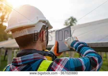Engineer Inspecting Or Repairing Solar Cells On A Solar Farm, Checking The Voltage With A Tablet.