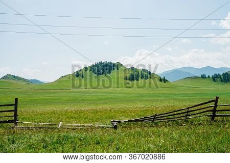 Beautiful Sunny Landscape With Green Forest Mountain And Vast Field Behind Broken Old Wood Fence. Hi