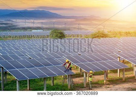 Engineering Team Inspecting Or Repairing Solar Cells On Solar Farms.