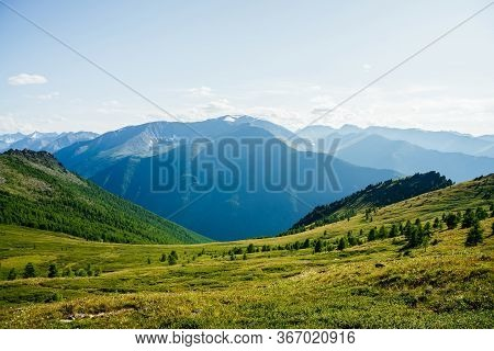 Beautiful Aerial View To Green Forest Valley And Great Snowy Mountains Far In Sunny Day. Awesome Alp
