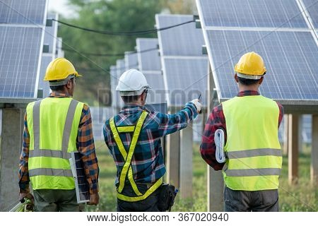 Engineering Team Inspecting And Repairing Solar Cells On Solar Farms Production Electricity Supply