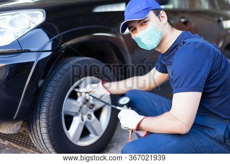 Masked mechanic inflating a tire, work during coronavirus concept