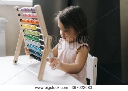 Inquisitive Beautiful Little Girl Is Playing With Multicolored Abacus While Sitting At The Table. Ch