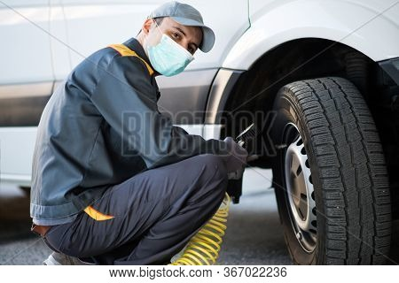 Masked mechanic checking the pressure of a van tire during coronavirus pandemic