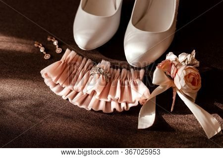 Wedding Accessories On The Wooden Table: A Bridal Grooms Boutonniere, Gold Earrings, White Shoes And