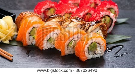 Sushi with chopsticks. Sushi roll japanese food in restaurant. California Sushi roll set with salmon, vegetables, flying fish roe and caviar closeup. Japan restaurant menu.
