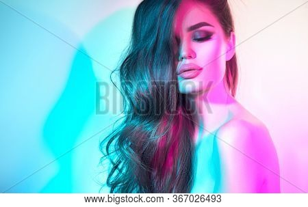 High Fashion model woman in colorful bright neon lights posing in studio, night club. Portrait of beautiful dancer girl in UV. Art design colorful make up. On colourful vivid blue with pink background