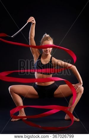 Artistic photo of young rhytmic gymnast doing ribbon exercise over black background.