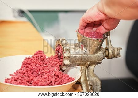 Minced Meat. Womans Hands Twist Manual Meat Grinder Through Which Minced Meat Comes Out. Minced Meat