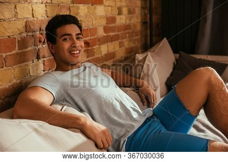 Smiling Mixed Race Man Chilling On Sofa In Living Room During Quarantine