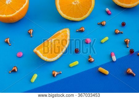 Multivitamins And Supplements With Fresh Orange On Blue Background.healthy Concept Image. Vitamin C