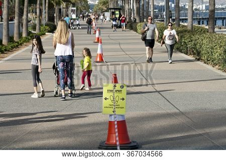 Limassol, Cyprus, May 13th, 2020: Seafront Promenade Molos With People Walking Along Red And White S