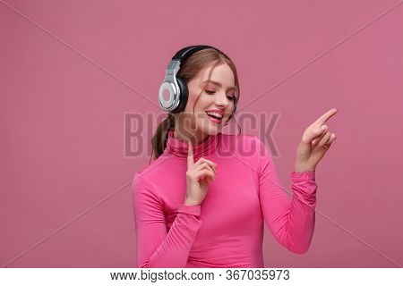 Enjoy Listening To Music. Beautiful Young Redhead Woman In Headphones Listening Music. Funny Smiling