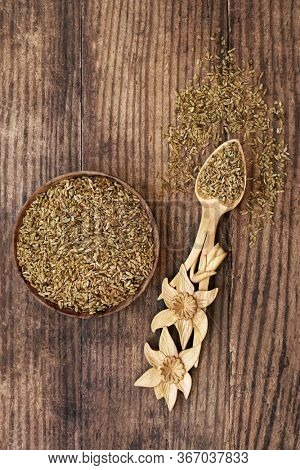 Freekeh grain health food in a bowl and daffodil lovespoon. Highly nutritious high in fibre, protein & treats IBS & digestive issues, with low gi for diabetics. Flat lay.