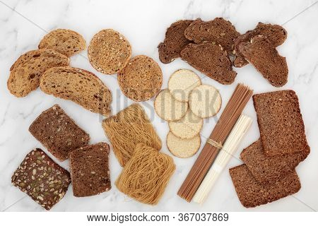 Low glycemic food for a diabetic diet with bread, pasta, oatmeal crackers & noodles, high in antioxidants & smart carbs. Below 55 on the GI index. Top view on marble.