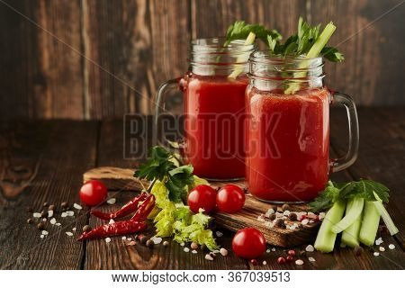 Two glasses with fresh tomato juice, celery, parsley, spices and ripe tomatoes on dark brown wooden background with copy space. Healthy beverage, vegetable juice