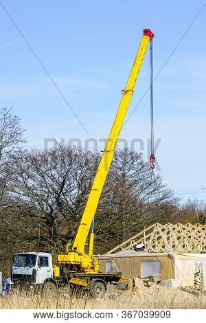 Truck Mounted Crane With A Telescoping Boom At Constructing A Carcas Of A New Wooden Building