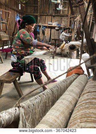Lung Tam, Vietnam - January 9, 2020 - Woman weaving in a traditional way, focus on the lin and the loom