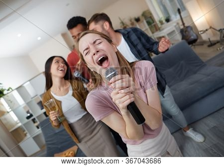 Karaoke Singer. Beautiful Young Girl Holding Microphone And Singing While Playing Karaoke With Best