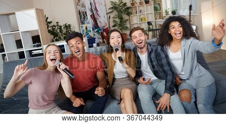 Home Entertainment. Group Of Young Happy Multicultural Friends Playing Karaoke At Home, Singing With