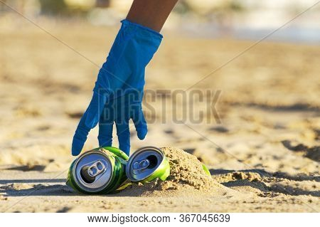 Clean Beach From Trash. Woman Hand Picking Up Empty Soft Drinks Cans Trash From The Beach