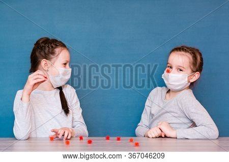 Girls In Medical Masks In Quarantine Play Viruses. Entertaining Children In Isolation In An Epidemic