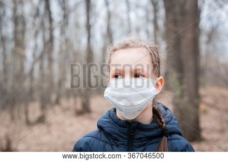 Epidemic Covid-19. A Girl In A Medical Mask Walks Alone In A Deserted Forest. Isolation And Quaranti