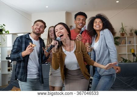 Young Asian Girl Holding Microphone And Singing While Playing Karaoke With Best Friends At Home. Gro