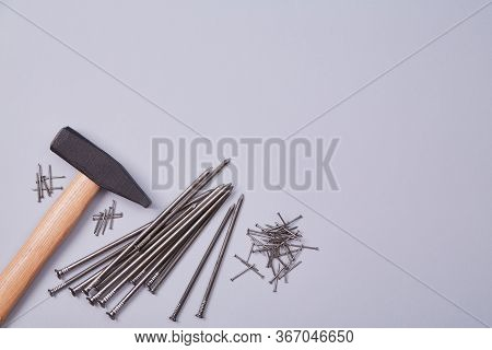 Building And Renovation Concept. Hammer Equipment And Different Sizes Of Tacks. Isolated On Wooden B
