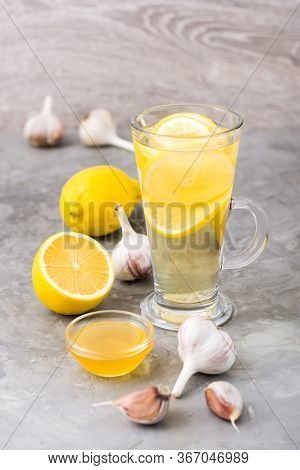 Therapeutic Drink Of Lemon, Honey And Garlic In A Glass On The Table. Alternative Medicine, Treatmen