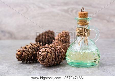 Cedar Oil In A Bottle And Cedar Cones On The Table. Treatment Of Resin Cedar. Alternative Medicine