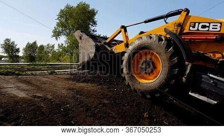 The Jcb All-wheel Drive Backhoe Loader Stands With Raised Backhoe Standing Over Blue Sky Made In Rus