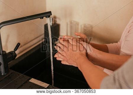 Cropped View Of Mother And Child Washing Hands In Kitchen