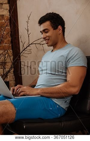 Smiling Mixed Race Man Chilling With Laptop At Home During Self Isolation