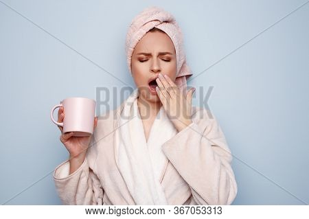Woman In Pink Bathrobe With Towel On Head Holding Cup Of Tea Or Coffee In Hand, After Shower At Morn