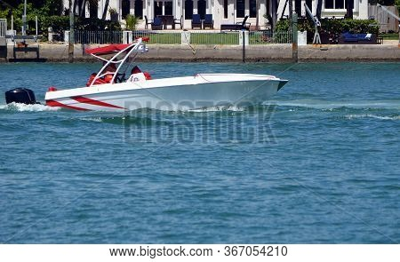 Well Appointed White With Red Trim Motor Boat Powered By A Single Outboard Engine.