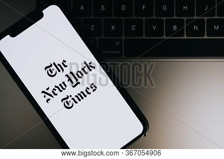Hands Holding Iphone X With The New York Times Logo On The Screen. Copy Space.