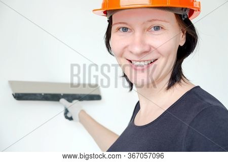 A Smiling Woman In A Helmet Holds A Putty Knife. Repair In The Apartment. Quick Repair. Repair Tips.