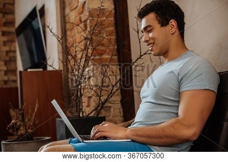 Happy Mixed Race Man Chilling With Laptop At Home On Quarantine