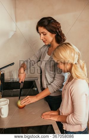 Side View Of Daughter Looking At Mother Cutting Apple On Kitchen Worktop