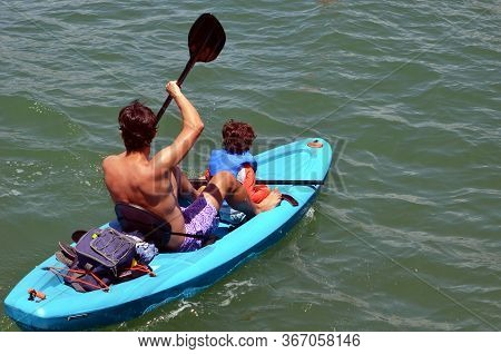 Father And His Toddler Son Kayaking Off Miami Beach On The Florida Intra-coastal Waterway.