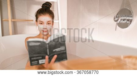 Woman reading book in warm bathtub taking a bath relaxing at home - pamper wellness Asian girl pampering skin care with facial mask treatment banner panorama.