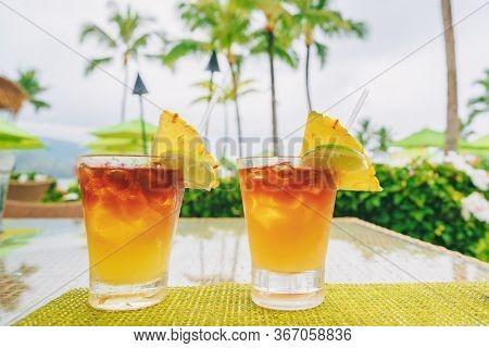 Hawaii mai tai drinks at resort hotel restaurant. Famous hawaiian rum based drink cocktails with view of beach, Hawaii tourist summer vacation destination.