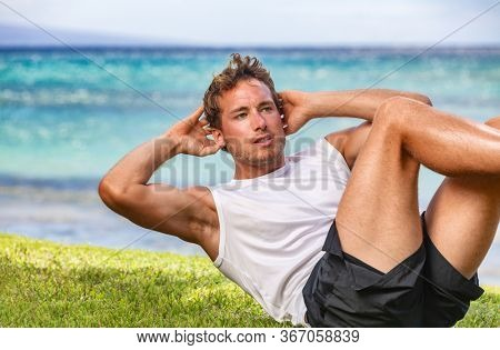 Fitness abs workout fit man training outdoor in park exercising for weight loss stomach six pack handsome guy. Beach summer elbow to knee crunch exercise.